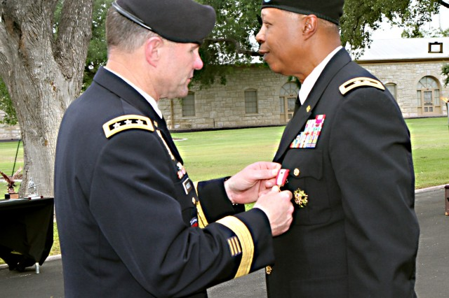 FORT SAM HOUSTON, Texas - Lt. Gen. Perry Wiggins (left), commanding general for U.S. Army North (Fifth Army) and senior commander for Fort Sam Houston and Camp Bullis, presents an Army Distinguished Service Medal to Maj. Gen. Adolph McQueen Jr., deputy commanding general for support, Army North, during McQueen's retirement ceremony Sept. 17 at the historic Quadrangle. McQueen's service to the nation began in 1971 when he enlisted in the U.S. Marine Corps.