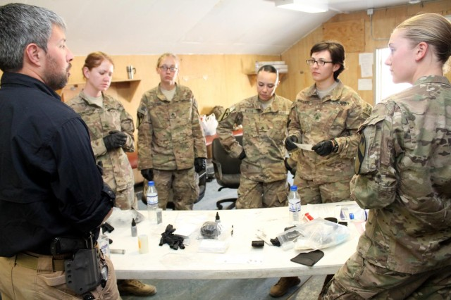 Combined Joint Task Force trainer Jean Paul Stassi explains the fundamentals of fingerprinting to Sgt. Katherine Restko, Staff Sgt. Melissa Telford, Cpl. Alice Curtis, Sgt. Leah Mallett and Spc. Jenna Bruxvoort, during Female Engagement Team training at Bagram Airfield, Afghanistan, Sept. 16, 2013.  The military intelligence analysts from the 2nd Brigade, 1st Cavalry Division, were the first to participate in a new three-day training course for Female Engagement Team members.