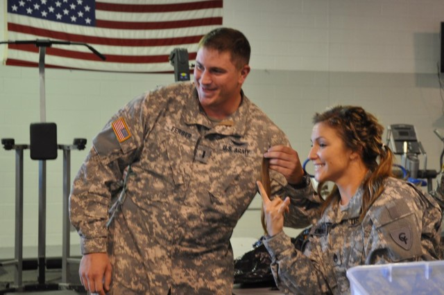 1st Lt. Jonathon Ferber (left) poses with Staff Sgt. Erin Emminger, both with the Indiana Army National Guard, after cutting a lock of her hair at the National Guard Armory in Shelbyville, Ind., Sept. 14, 2013. Emminger raised more than $1,000 to support Spc. Jeremiah Morgan's battle with his cancer. Emminger set out to shave her head if she raised $500.