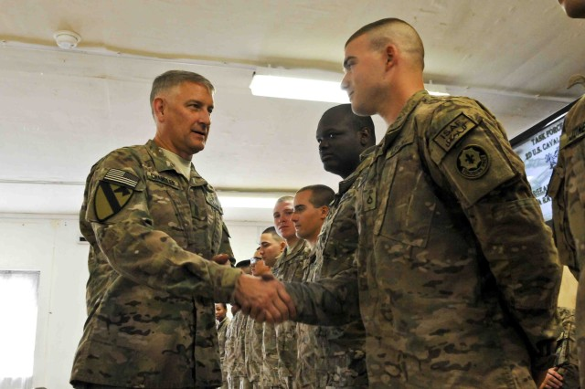 Sgt. Maj. of the Army Raymond F. Chandler III (left), senior enlisted advisor for the U.S. Army, recognizes a Soldier with Combined Task Force Dragoon by giving him a coin during a visit, Sept. 22, 2013, at Forward Operating Base Walton, Afghanistan. Chandler visited bases in southern Afghanistan to address concerns the Soldiers might have regarding current and upcoming events in the Army.