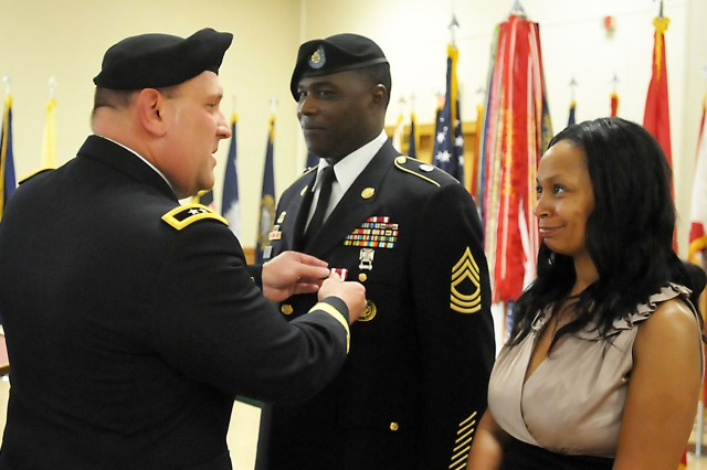Maj. Gen. John Wharton pins the Meritorious Service Medal on Master Sgt. Andre James flanked by his wife, Gaarett. James is assigned to Headquarters and Headquarters Troop, Regional Support Squadron, 2nd Cavalry Regiment, Vilseck, Germany. He will retire with 22 years of service. (Photo by Jon Micheal Connor, ASC Public Affairs)
