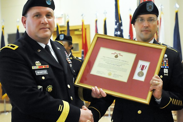 Sgt. 1st Class Larry Burden, U.S. Army Sustainment Command, assisted by Maj. Gen. John Wharton, displays his Meritorious Service Medal for 21 years of service. (Photo by Jon Micheal Connor, ASC Public Affairs)
