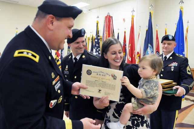 "It's all smiles as Merrick Morley, 1, receives an ""Army Brat"" certificate of appreciation from Maj. Gen. John Wharton, as Staff Sgt. Robert Morley, retiring, and his wife, Nicole, look on. (Photo by Jon Micheal Connor, ASC Public Affairs)"