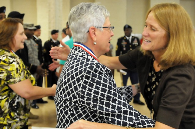 Teresa Brown, Army civilian, U.S. Army Sustainment Command, receives a hug following the ceremony. (Photo by Jon Micheal Connor, ASC Public Affairs)