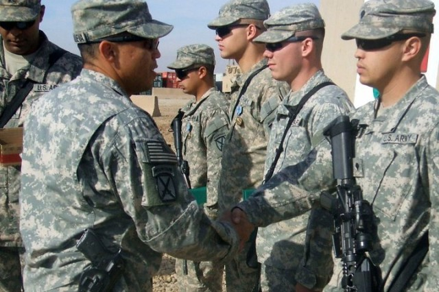 Master Sgt. Gregorio Villanuevaochoa gives awards to his Soldiers while stationed in Iraq, in 2010.