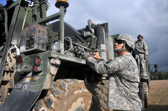 GRAFENWOEHR, Germany -- Staff Sgt. Sung Lee, a mechanic with the 21st Theater Sustainment Command's 18th Combat Sustainment Support Battalion, 16th Sustainment Brigade and a native of Los Angeles, operates the controls of a crane while trying to recover an overturned vehicle during the Wheeled Vehicle Recovery Course Sept. 19. Twenty Soldiers from the 21st TSC participated in the training to learn how to recover stuck and rolled vehicles as well as how to safely tow them for prolonged distances.  (Photo by Staff Sgt. Warren W. Wright Jr., 21st TSC Public Affairs)