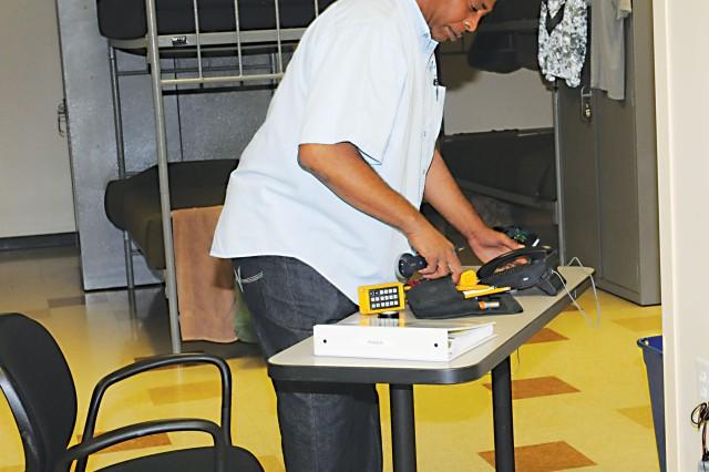 Kevin Mavity, telecom technician for NEC, installs the SHARP hotline Friday in the Bender Barracks on Harmony Church.