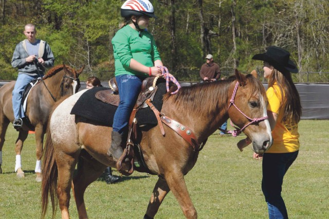 A young girl is guided on a horse during the Warrior Outreach Horsemanship event April 6. More than 1,100 Soldiers and Family members participated.
