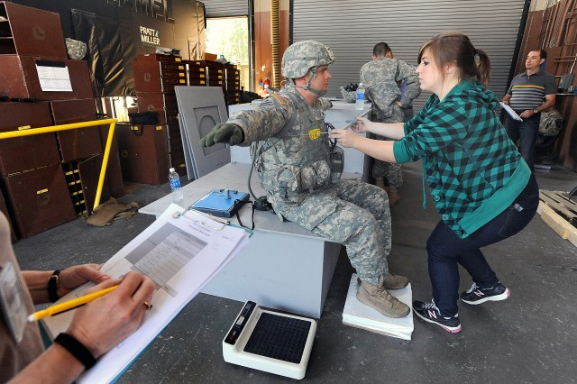 Christine Sniezek, an engineer with the Army's Natick Soldier Research, Development & Engineering Center, takes Spc. Nathan Rawlins' measurements.