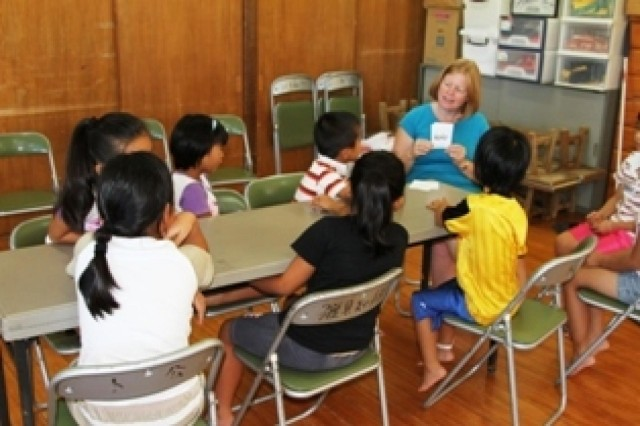 Jennifer Toland, a volunteer from the 10th Regional Support Group, helps local Japanese students learn English during a class Aug. 27 at the Toguchi Community Center. The class is part of United States Army Japan Garrison Torii Station and 10th RSG community relations program to help build a healthy relationship.