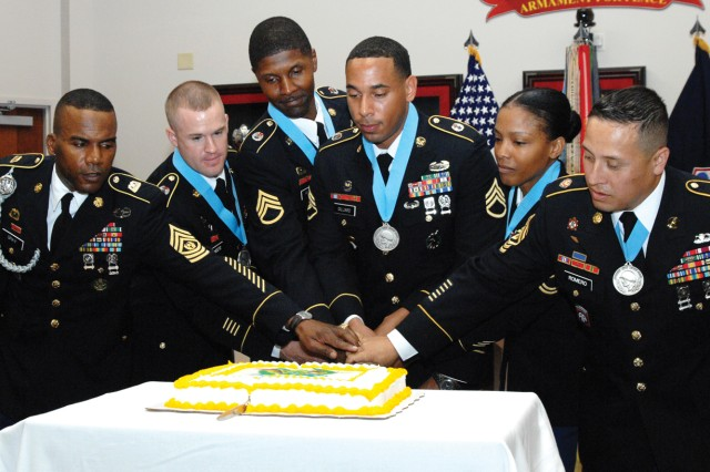The participants of the Sept. 20 Audie Murphy Club induction ceremony in Ball Auditorium cut a ceremonial cake at the conclusion of the event. Joining the four inductees are Command Sgt. Maj. Spencer Gray, Quartermaster Corps Regimental CSM, left, and 1st Sgt. Oscar Romero, president of the AMC's Fort Lee Chapter.