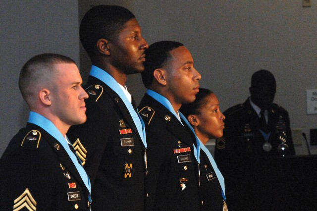 Four new Audie Murphy Club members proudly accept a round of applause at the conclusion of a Sept. 20 induction ceremony in Ball Auditorium. The new inductees are Staff Sgt. Richard Sheetz, Staff Sgt. Howard, Parker, Staff Sgt. Maurice Gillard and Sgt. 1st Class Peta-gail Rodney