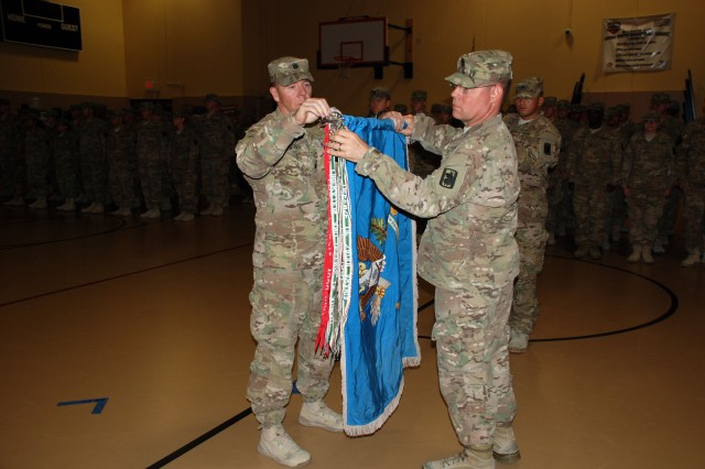Lt. Col. Joe Barber and Command Sgt. Maj. Joseph Williams uncased the battalion's colors, symbolizing the official return of the battalion to Joint Base San Antonio after a year in Afghanistan. (U.S. Army photo by Gregory Ripps, 470th Military Intelligence Brigade)