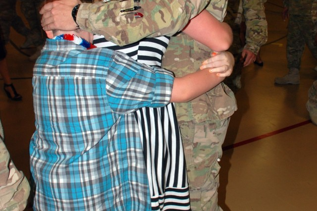 A Soldier receives a double embrace by his loved ones after reuniting Sept. 22. He and more than 100 other members of the 201st returned to Joint Base San Antonio-Fort Sam Houston following a year-long deployment to Afghanistan. The welcome-home event took place in the post's teen activity center. (U.S. Army photo by Gregory Ripps, 470th Military Intelligence Brigade)