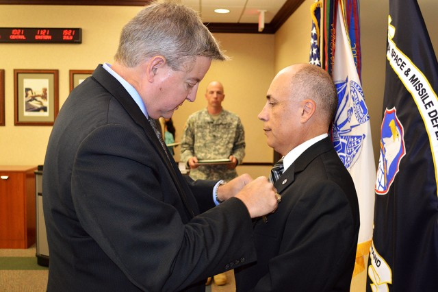Ronald Chronister, deputy to the commander, U.S. Army Space and Missile Defense Command/Army Forces Strategic Command, pins the Meritorious Civilian Service Medal onto Jerry Esquibel, chief, Advance Hypersonic Weapons Division, Rapid Transitions Directorate, SMDC's Technical Center, during Esquibel's retirement Sept. 24 at the command's Redstone Arsenal, Ala., headquarters. Esquibel retires with 33 years of federal service.
