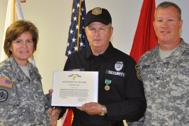 """Joint Munitions Command commander Brig. Gen. Kristin K. French (L)  and Blue Grass Army Depot commander Col. Lee Hudson award Blue Grass Army Depot security guard and Somerset, Ky., native Jeffrey Davis the """"Commander's Award for Civilian Service""""."""
