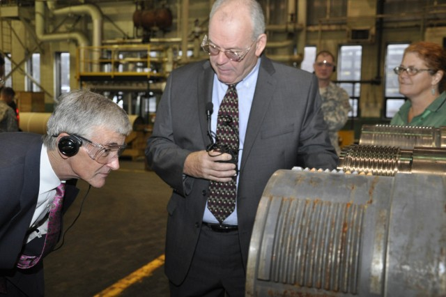 Secretary of the Army John McHugh takes a look down a 155mm tube at the detail that is required, while Arsenal Deputy Commander Ed McCarthy explains the quality control process.
