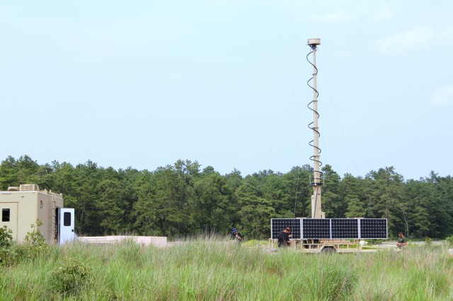 U.S. Army CERDEC engineers set up the Reduced Manning Situational Awareness system at a field testing event in June. Solar panels power the array of surveillance cameras at the top of the mast.