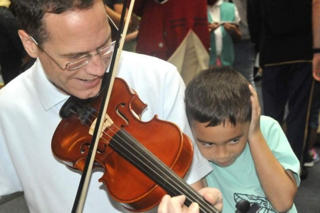 Five-year-old Evan Mollard (right) is less than pleased with the violin playing of his father, Andy Mollard, at  Musical Stories for Kids of All Ages at Joint Base Myer-Henderson Hall's Brucker Hall Sept. 21. The concert and musical meet and greet was hosted by The U.S. Army Band with The Old Guard Fife and Drum Corps also participating in the musical morning.