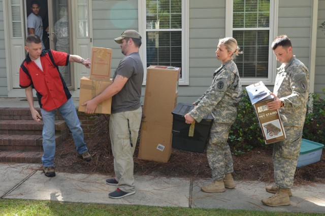 Chief Warrant Officer 5 Charles Petrie, an Army officer who has given almost 30 years to his country and is now terminally ill, directs volunteers carrying boxes of his family's household goods to specific rooms into their new home. Petrie was diagnosed with sarcoma in his sinus -- one of the rarest forms of cancer and in the rarest place, according to his wife, Terri. Despite multiple, large radiation treatments that shrank the tumor, the cancer is growing again. After being contacted by someone close to the family, U.S Army W.T.F! Moments took action by posting a message to their Facebook audience of more than 328,000 people. Approximately 100 Soldiers, retirees, and civilians showed up to help a fellow Soldier in need, Sept. 27, 2013, at a home in Fayetteville, N.C.