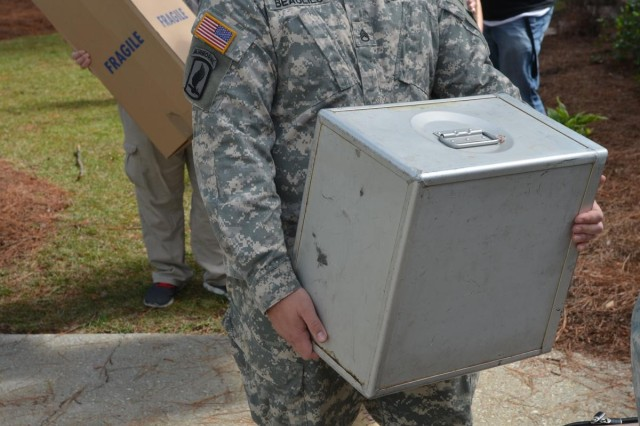 Staff Sgt. Christopher Beaulieu, 98th Civil Affairs Battalion, a volunteer from the Fayetteville community, stands in line, holding a box of household goods he helped unload from a self-storage container to assist Chief Warrant Officer 5 Charles Petrie, an Army officer who has given almost 30 years to his country and is now terminally ill, and his family with their move. Petrie was diagnosed with sarcoma in his sinus -- one of the rarest forms of cancer and in the rarest place, according to his wife, Terri. Despite multiple, large radiation treatments that shrank the tumor, the cancer is growing again. After being contacted by someone close to the family, U.S Army W.T.F! Moments took action by posting a message to their Facebook audience of more than 328,000 people. Approximately 100 Soldiers, retirees, and civilians showed up to help a fellow Soldier in need, Sept. 27, 2013, at a home in Fayetteville, N.C.