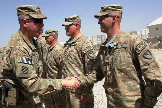 Command Sgt. Maj. Alan Hummel, senior enlisted leader, 4th Infantry Brigade Combat Team, 3rd Infantry Division, and a native of Pittsburgh, Pa., congratulates Sgt. Jesse Harrington, a Porterville, Calif., native and an adviser with the 36th Engineer Brigade, from Fort Hood, Texas, during a ceremony, Sept. 25, 2013, on Camp Maiwand, Afghanistan. The ceremony marked the end of the advisory team's mission to advise and assist the Afghan National Army's 4th Infantry Brigade, 203rd Corps's staff.
