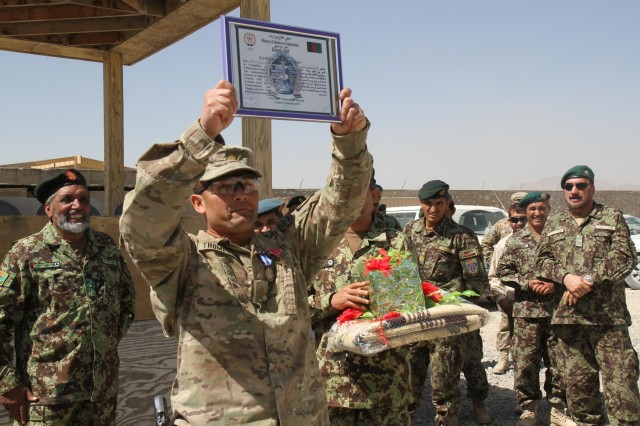 Maj. Christian Thompson, a native of Larned, Kan., and an adviser with the 36th Engineer Brigade, attached to the 4th Infantry Brigade Combat Team, 3rd Infantry Division, raises a certificate presented to him by staff members of the 4th Infantry Brigade, 203rd Corps, Afghan National Army, Sept. 25, 2013, on Camp Maiwand, Afghanistan, during a ceremony that marked that end of his team's advisory mission to the ANA in eastern Afghanistan.