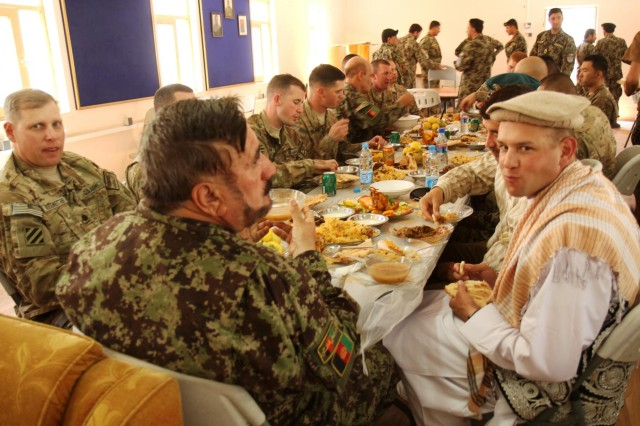 Capt. Todd Stawicki (right), a native of Bridgewater, N.J., and an adviser with the 36th Engineer Brigade, attached to the 4th Infantry Brigade Combat Team, 3rd Infantry Division, wears traditional Afghan clothing given to him by staff members of the Afghan National Army's 4th Infantry Brigade, 203rd Corps, during a lunch hosted by the ANA, Sept. 25, 2013, on Camp Maiwand, Afghanistan. The lunch followed an award ceremony that marked the end of his team's advisory mission to the ANA.