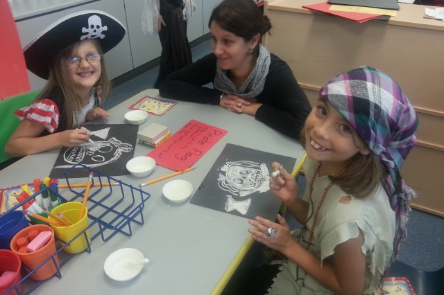 Priscilla Whorton (L) and Athena Duenas (R) create their own pirate flags under the tutelage of parent volunteer Melanie Pinson during International Talk Like A Pirate Day at Hohenfels Elementary School, recently.
