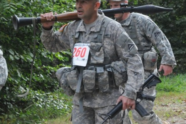 Command Sgt. Maj. Andre S. Machado lugs along a 15-pound 'dummy' RPG launcher to add more challenge for the JMRC Vampires team during the U.S. Forces Europe Combat Cross Country Championships at Hohenfels, Sept. 27.