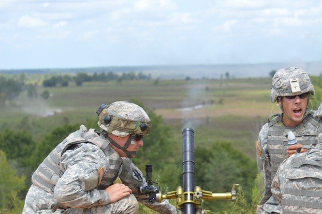 Spc. Zack Farrow, an assistant mortar gunner with Charlie Troop, 1st Squadron 108th Cavalry Regiment, 48th Infantry Brigade Combat Team, prepares to send another mortar downrange during a combined arms live fire exercise. (U.S. Army photo by Sgt. 1st Class Stephanie Widemond, 188th Infantry Brigade Public Affairs)