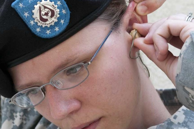 "Staff Sgt. Nicole Gillespie inserts the Combat Arms Earplugs"" in her ear to protect against sustaining a hearing injury."