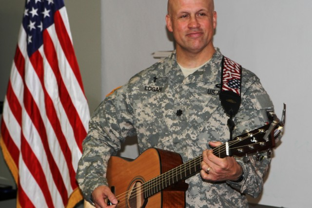 Lt. Col. Jason Logan, Division East Training Chaplain, plays guitar during a Division East prayer breakfast held Sept. 26, 2013.  The breakfast focused on recognizing the role of noncommissioned officers, their role as shepherds of Soldiers, and showing how a deep-seated faith can increase their spiritual resilience. (U.S. Army photo by Staff Sgt. Stephen Crofoot, First Army Division East Public Affairs)