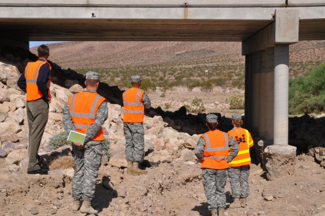 USACE South Pacific Division Commander Brig. Gen. David Turner and staff from the Los Angeles District view the path of mud flow and debris that eroded the gravel and riprap away from the support coloumns at Bridge 13, Fort Irwin, Calif., Sept. 19.