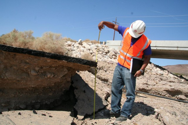 USACE Los Angeles District Civil Engineer Tony Rocha, measures a disintergraded bicycle and walking pathway as he assess damage near and arouond bridge 13 at Fort Irwin, Calif., Aug. 29.  A strong monsoon like storm caused flooding and excessive scouring at the fort Aug. 25.