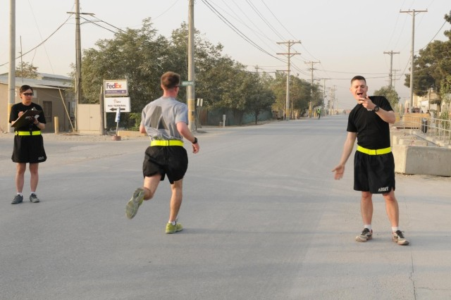 Capt. Eric F. Prazinko, a native of Ozark, Ala., and commander of the 101st Special Troops Battalion, 101st Sustainment Brigade, 101st Airborne Division (Air Assault), shouts out the run time to 1st Lt. Timothy S. Ladwig, a native of Minocqua, Wis., and battle captain with Task Force Lifeliner, who was the first runner to complete the 3 mile run in the 101st Special Troops Battalion Iron Dawg competition, Sept. 28, 2013, at Bagram Air Field, Parwan province, Afghanistan. Sgt. Shantelle Kamei, a native of Wahiawa, Hawaii, is the score tracker during this run. This competition is to promote espirit de corps within the Task Force Lifeliner units. (U.S. Army photo by Sgt. Sinthia Rosario, Task Force Lifeliner Public Affairs)