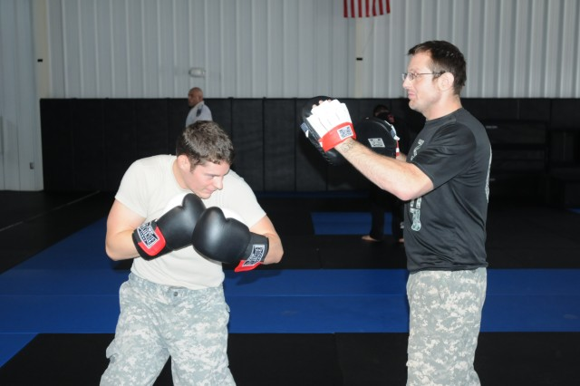 Sgt. William Tucker, left, of D Troop, 1st Squadron, 16th Cavalry Regiment, 316th Cavalry Brigade, does combatives training with Jason Keaton, brigade combatives director, at the brigade combatives gym on Harmony Church.