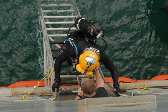 Pfc. Cody Callahan lowers Spc. Sam Schreier, both Army divers with the 7th Dive Detachment, 130th Engineer Brigade, into the water, Oct. 1, 2013, from a logistics support vessel docked at a pier at Joint Base Pearl Harbor-Hickam, Hawaii, during Deep Blue, an annual exercise designed to reinforce safety and tactical proficiency during dive operations.