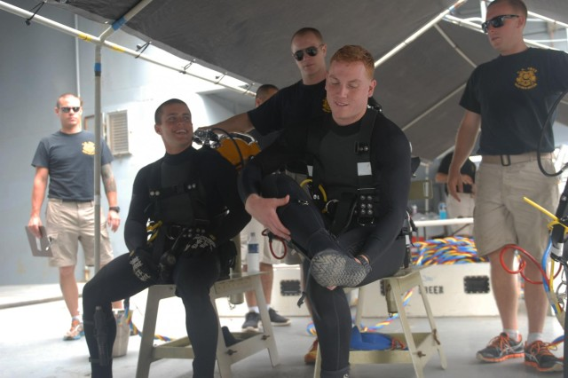 Sgt. Dakota Rager (sitting left) and Spc. Sam Schreier (sitting right), both Army divers with the 7th Engineer Dive Detachment, 130th Engineer Brigade, suit up, Oct. 1, 2013, during Deep Blue, an annual exercise designed to reinforce safety and tactical proficiency during dive operations at Joint Base Pearl Harbor-Hickam, Hawaii.
