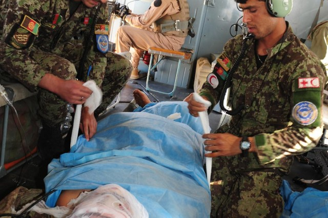 Afghan air force flight medics Sgt. Kamran Saboon (left) and soldier Saddam Parishan (right), both with the Kandahar Air Wing, take care of an injured soldier during a casualty evacuation mission near Ghorak, Afghanistan, Sept. 23, 2013. The NATO Air Training Command-Afghanistan advisers of the 738th Air Expeditionary Advisory Group, have been stepping back as the Kandahar Air Wing steps up and executes more casualty evacuation missions on their own with minimal oversight from their advisers.