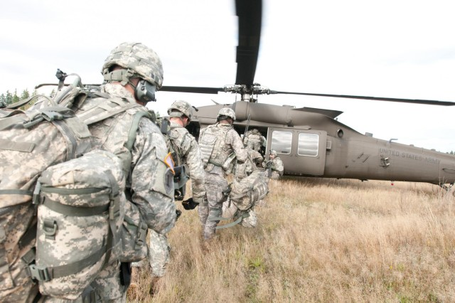 The Soldiers of the 571st Sapper Company, practiced their air assault skills rushing to an arriving Black Hawk helicopter during training at the Leschi Town training area on Joint Base Lewis-McChord, Wash., Sept. 23, 2013. During the training, the soldiers were inserted and extracted near the mock city where they cleared houses and confronted simulated enemy forces.
