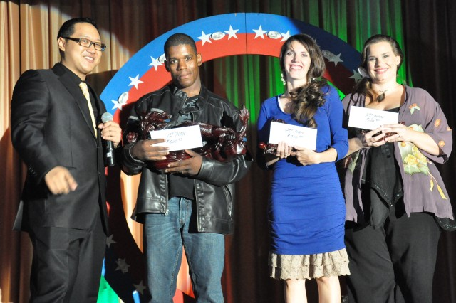 Program emcee Lorenzo Ranches presents Spc. Ikilya Davenport, Sara Isom and Ariane Pardubsky with their winnings for finishing in the top three of the Camp Humphreys 2013 Operation Rising Star competition Sept. 27.