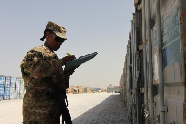 Sgt. Sharmella Andrews verifies information on the outside of a container at the logistics retrograde area at Kandahar Airfield, Afghanistan, Sept. 13, 2013. Andrews, the logistics and supply non-commissioned officer in charge of Detachment 33, is assigned to the 335th Signal Command, Theater Provisional, Regional Command South.