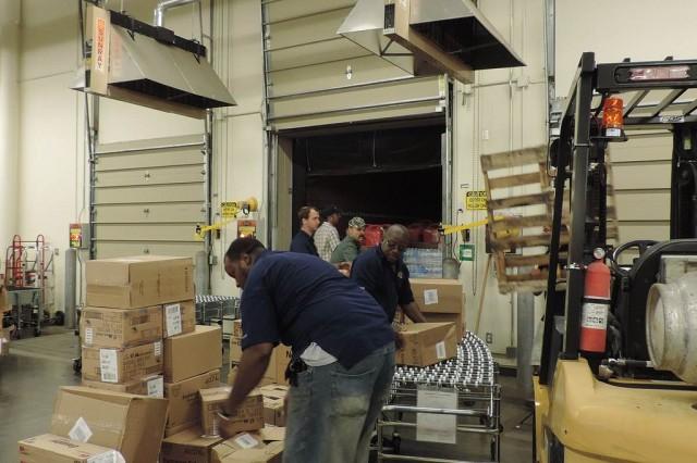Keelser Exchange associates unload a trailer of emergency supplies in preparation for Tropical Storm Karen.
