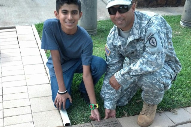 "Staff Sgt. Carlos Ramirez, Jr. and his son Carlos Ramirez III help lay some of the hundreds of new brick pavers that expanded the courtyard adjacent to the memorial, known as ""Unified Through Sacrifice Memorial"", at the 25th Inf. Div. Headquarters Building on Schofield Barracks, Hawaii. The new expansion doubles the size of the previous footprint, allowing for more room to pay tribute to the Soldiers: past and present."
