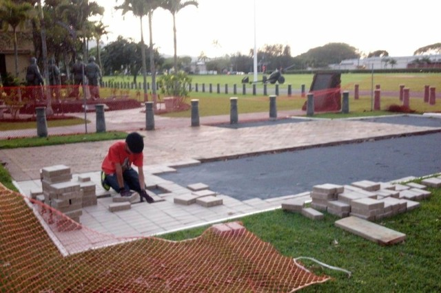"""Soldiers and volunteers help to lay some of the hundreds of new brick pavers that expanded the courtyard adjacent to the memorial, known as """"Unified Through Sacrifice Memorial"""", at the 25th Inf. Div. Headquarters Building on Schofield Barracks, Hawaii. The new expansion doubles the size of the previous footprint, allowing for more room to pay tribute to the Soldiers, past and present."""