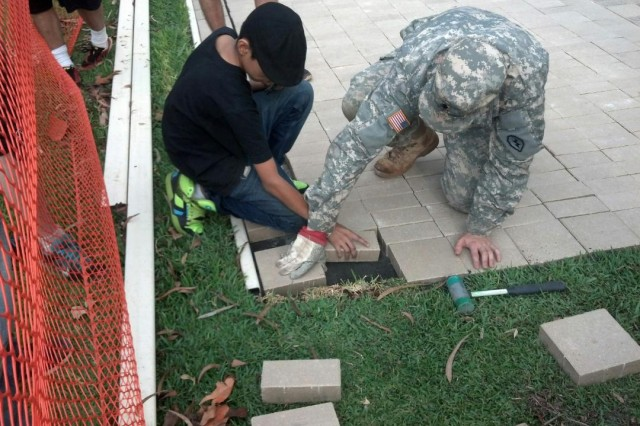 """Staff Sgt. Carlos Ramirez, Jr. and his son Carlos Ramirez III help lay some of the hundreds of new brick pavers that expanded the courtyard adjacent to the memorial, known as """"Unified Through Sacrifice Memorial"""", at the 25th Inf. Div. Headquarters Building on Schofield Barracks, Hawaii. The new expansion doubles the size of the previous footprint, allowing for more room to pay tribute to the Soldiers: past and present."""