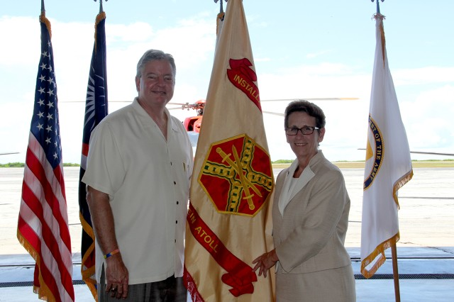 Ronald Chronister, deputy to the commander, U.S. Army Space and Missile Defense Command/Army Forces Stragetic Command, and Debra Zedalis, director of Installation Management Command-Pacific, stand with the newly uncased IMCOM headquarters flag at U.S. Army Garrison, Kwajalein Atoll Oct. 2.