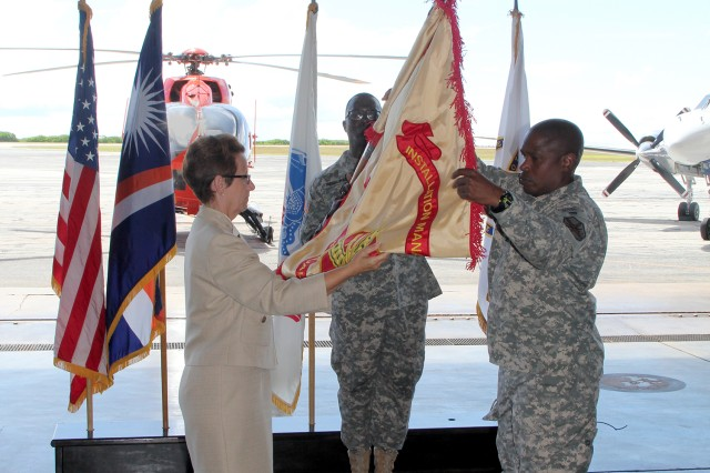 From left, Debra Zedalis, Installation Management Command-Pacific director, Col. Nestor Sadler, U.S. Army Garrison, Kwajalein Atoll commander, and Sgt. Maj. Roderick Prioleau, USAG-KA command sergeant major, uncase the Installation Management Command flag, signifying the transfer of headquarters from the U.S. Army Space and Missile Defense Command/Army Forces Strategic Command to IMCOM Oct. 2.