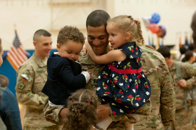 Capt. Matthew Pride, commander, Headquarters and Headquarters Company, 555th Engineer Brigade, hugs his children during a homecoming ceremony at Wilson Sports and Fitness Center on JBLM, Oct. 4. Pride returned home from a nine-month deployment to Afghanistan in support of Operation Enduring Freedom.